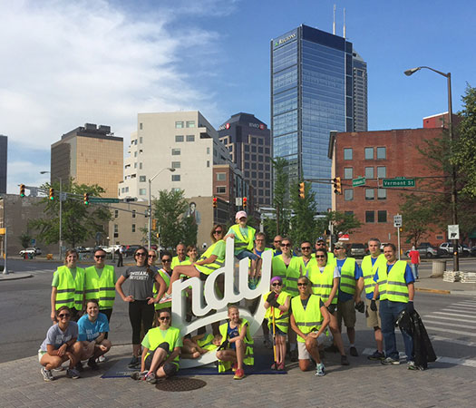 "Downtown Indy employees pose for a picture with the ""INDY"" sculpture after the Mass Ave Clean Up."